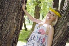 Glückliche blonde junge Frau im Park oben lächelnd, Blumenabschluß Lizenzfreie Stockfotos
