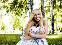 Glückliche blonde junge Frau im Park oben lächelnd, Blumenabschluß Stockbild