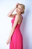 Glückliche blonde junge Frau im rosa Kleid Lizenzfreies Stockfoto