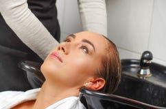 Glückliche blonde junge Frau mit waschendem Kopf des Friseurs am Friseursalon, an der Schönheit und am Leutekonzept Lizenzfreie Stockfotos