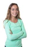 Glückliche blonde kaukasische Frau mit blauen Augen und den gekreuzten Armen Lizenzfreie Stockfotos