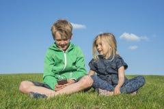 Glückliche blonde Kinder, die den Smartphone verwenden (aufpassendes Film- oder spielenspiel) sitzend auf dem Gras Stockfotografie