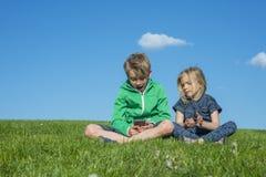 Glückliche blonde Kinder, die den Smartphone verwenden (aufpassendes Film- oder spielenspiel) sitzend auf dem Gras Lizenzfreie Stockfotografie