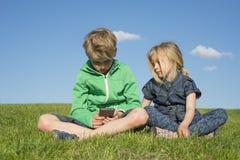 Glückliche blonde Kinder, die den Smartphone verwenden (aufpassendes Film- oder spielenspiel) sitzend auf dem Gras Stockfoto