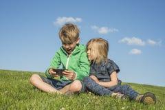 Glückliche blonde Kinder, die den Smartphone verwenden (aufpassendes Film- oder spielenspiel) sitzend auf dem Gras Stockbild