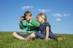Glückliche blonde Kinder, die den Smartphone verwenden (aufpassendes Film- oder spielenspiel) sitzend auf dem Gras Lizenzfreies Stockfoto