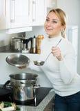Glückliche blonde kochende Suppe zu Hause Stockfotos