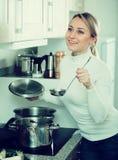 Glückliche blonde kochende Suppe zu Hause Stockfoto
