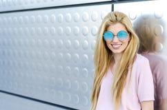 Glückliche blonde lächelnde lokalisierte Sonnenbrille der jungen Frau Stockfotografie