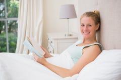 Glückliche blonde Lesung ihr Buch Lizenzfreie Stockbilder