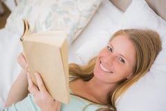 Glückliche blonde Lesung ihr Buch Stockfotografie