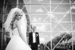 Glückliche blonde Luxusbraut und eleganter Bräutigam auf dem Hintergrund O Lizenzfreie Stockfotos