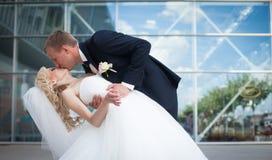 Glückliche blonde Luxusbraut und eleganter Bräutigam auf dem Hintergrund O Lizenzfreie Stockbilder