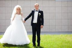 Glückliche blonde Luxusbraut und eleganter Bräutigam auf dem Hintergrund O Lizenzfreies Stockbild