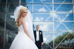 Glückliche blonde Luxusbraut und eleganter Bräutigam auf dem Hintergrund O Stockfotos