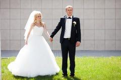 Glückliche blonde Luxusbraut und eleganter Bräutigam auf dem Hintergrund O Lizenzfreie Stockfotografie