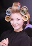 Glückliche blonde Mädchenhaarlockenwicklerrollen durch haidresser im Schönheitssalon Lizenzfreies Stockfoto