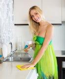 Glückliche blonde Mädchenreinigungsmöbel in der Küche Stockfotografie