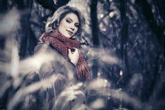 Glückliche blonde Modefrau, die in Herbstwald geht Stockfotos