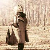 Glückliche blonde Modefrau mit dem Handtaschengehen im Freien Lizenzfreie Stockfotografie