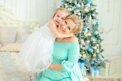 Glückliche blonde Mutter, die blaues Kleid trägt und kleine Tochter nahe Weihnachtsbaum umarmt Lizenzfreie Stockfotos
