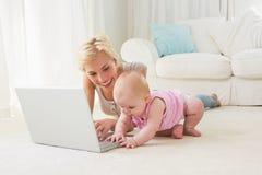Glückliche blonde Mutter mit ihrem Baby, das Laptop verwendet Lizenzfreie Stockfotografie
