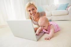 Glückliche blonde Mutter mit ihrem Baby, das Laptop verwendet Stockfotografie