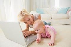 Glückliche blonde Mutter mit ihrem Baby, das Laptop verwendet Lizenzfreie Stockbilder