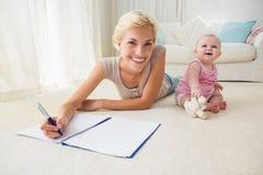Glückliche blonde Mutter mit ihrem Babyschreiben auf einem Schreibheft Stockfotografie