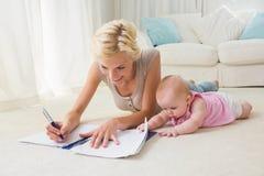 Glückliche blonde Mutter mit ihrem Babyschreiben auf einem Schreibheft Lizenzfreies Stockbild