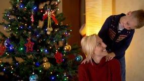 Glückliche blonde Mutter mit ihrem Sohn unter einem Weihnachtsbaum stock footage