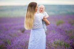 Glückliche blonde Mutter und ihr kleiner Sohn, die Spaß auf einem Lavendelgebiet hat Lizenzfreie Stockbilder