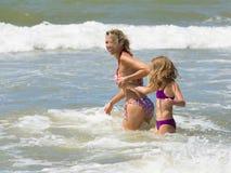 Glückliche blonde Mutter und Tochter spielen unter Wellen von Meer Lizenzfreie Stockfotos