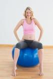 Glückliche blonde schwangere Frau, die auf Übungsball sitzt Lizenzfreies Stockfoto