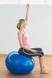 Glückliche blonde schwangere Frau, die auf Übungsball trainiert Stockfotos