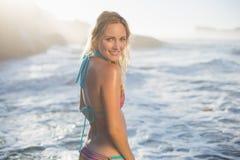 Glückliche blonde Stellung auf dem Strand im Bikini, der an der Kamera lächelt Stockbilder