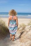 Glückliche blonde Stellung im Meer, das an einem sonnigen Tag aufwirft Stockbild