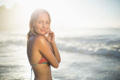 Glückliche blonde Stellung im Meer, das im Bikini aufwirft Stockbild