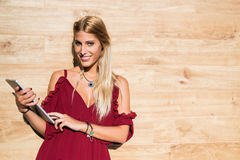 Glückliche blonde Studentenfrau, die eine Tablette und ein Lächeln verwendet Stockfoto