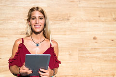 Glückliche blonde Studentenfrau, die eine Tablette und ein Lächeln verwendet Stockbilder