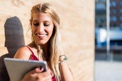Glückliche blonde Studentenfrau, die eine Tablette und ein Lächeln verwendet Lizenzfreie Stockfotos