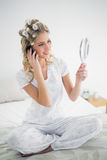 Glückliche blonde tragende Haarlockenwickler, die Reflexion während pH betrachten Stockfotografie