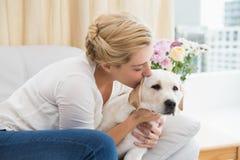 Glückliche blonde Umarmung mit Welpen auf Sofa Stockfoto