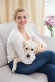 Glückliche blonde Umarmung mit Welpen auf Sofa Lizenzfreie Stockbilder