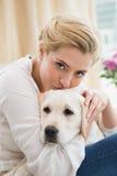 Glückliche blonde Umarmung mit Welpen auf Sofa Stockbilder