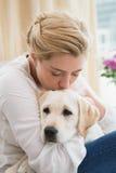Glückliche blonde Umarmung mit Welpen auf Sofa Lizenzfreie Stockfotografie