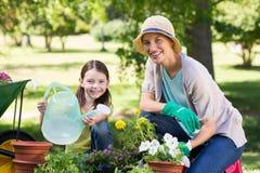 Glückliche blonde und ihre Tochtergartenarbeit Lizenzfreie Stockfotos