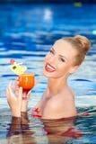 Glückliche Blondine, die ein Getränk während in einem Pool hält Stockfoto