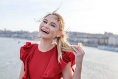 Glückliche Blondine im roten Kleiderlachen Stockbilder