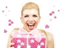 Glückliche Blondine mit Puzzlespielgeschenkkasten Lizenzfreie Stockbilder